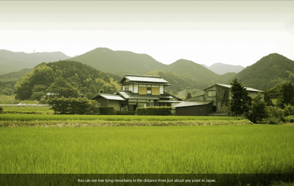 A house and rice field with low-lying mountains in the distance.